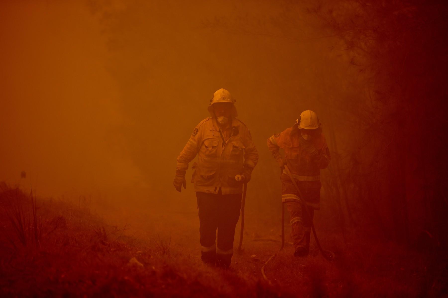 Hasiči bojují proti požáru v hustém kouři ve městě Moruya, jižně od Batemans Bay, v Novém Jižním Walesu
