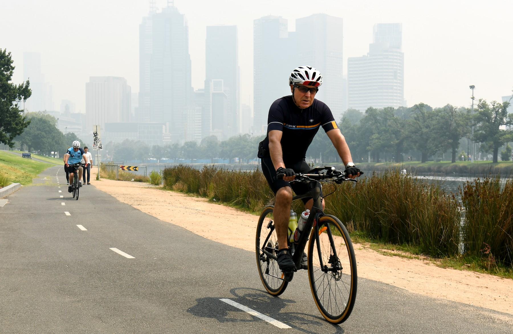 Cyklista projíždí oparem kouře v Melbourne