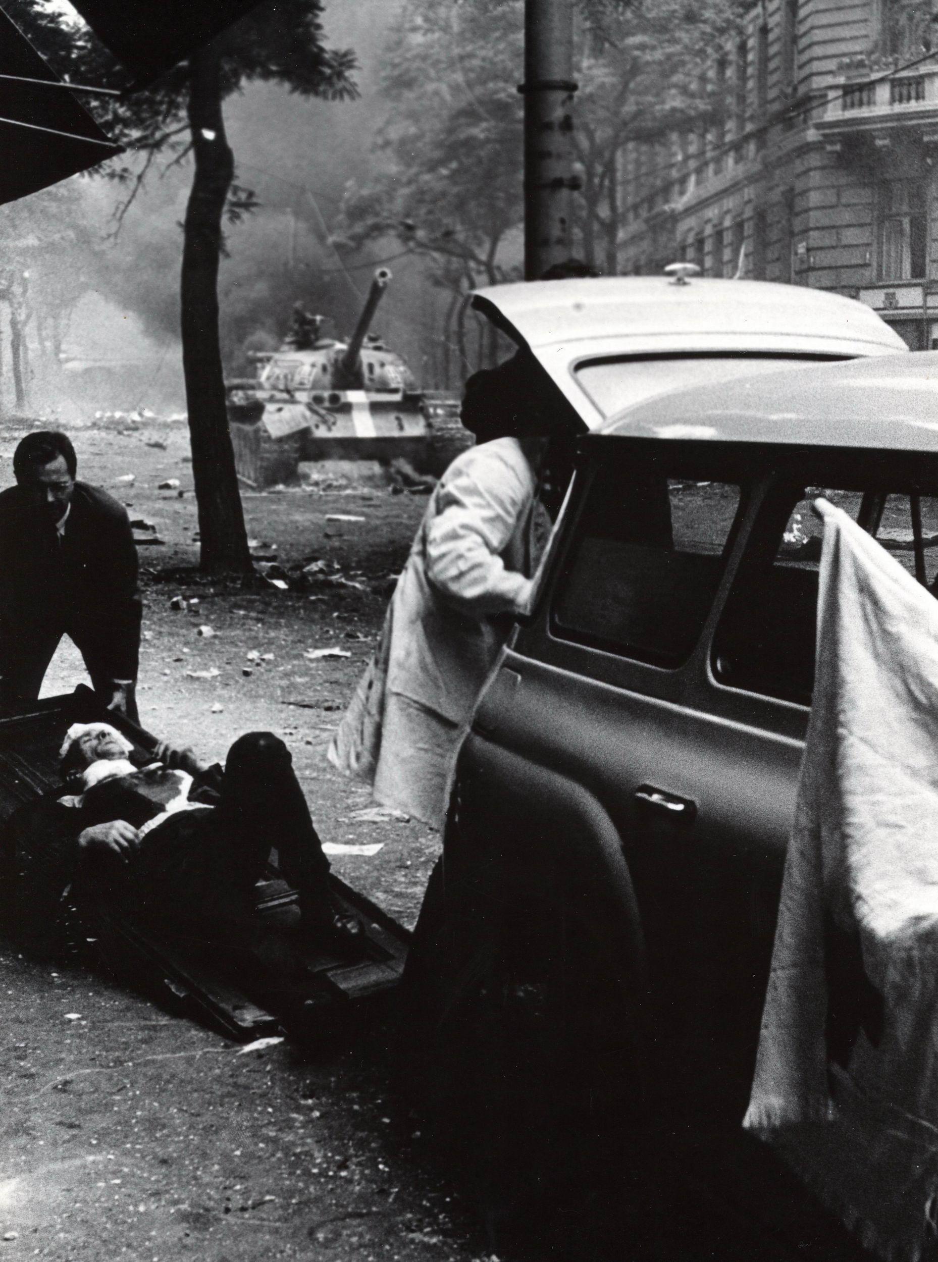 Raněný na nosítkách, za ním tank s pruhem. Podívejte se na nejlepší fotky z roku 1968