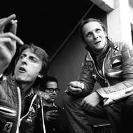 čtk: Niki Lauda s chlebem ruce v paddocku, vedle něj gestikuluje ředitel Ferrari Luca di Montezemolo. Německo, Nürburg, nedatováno.