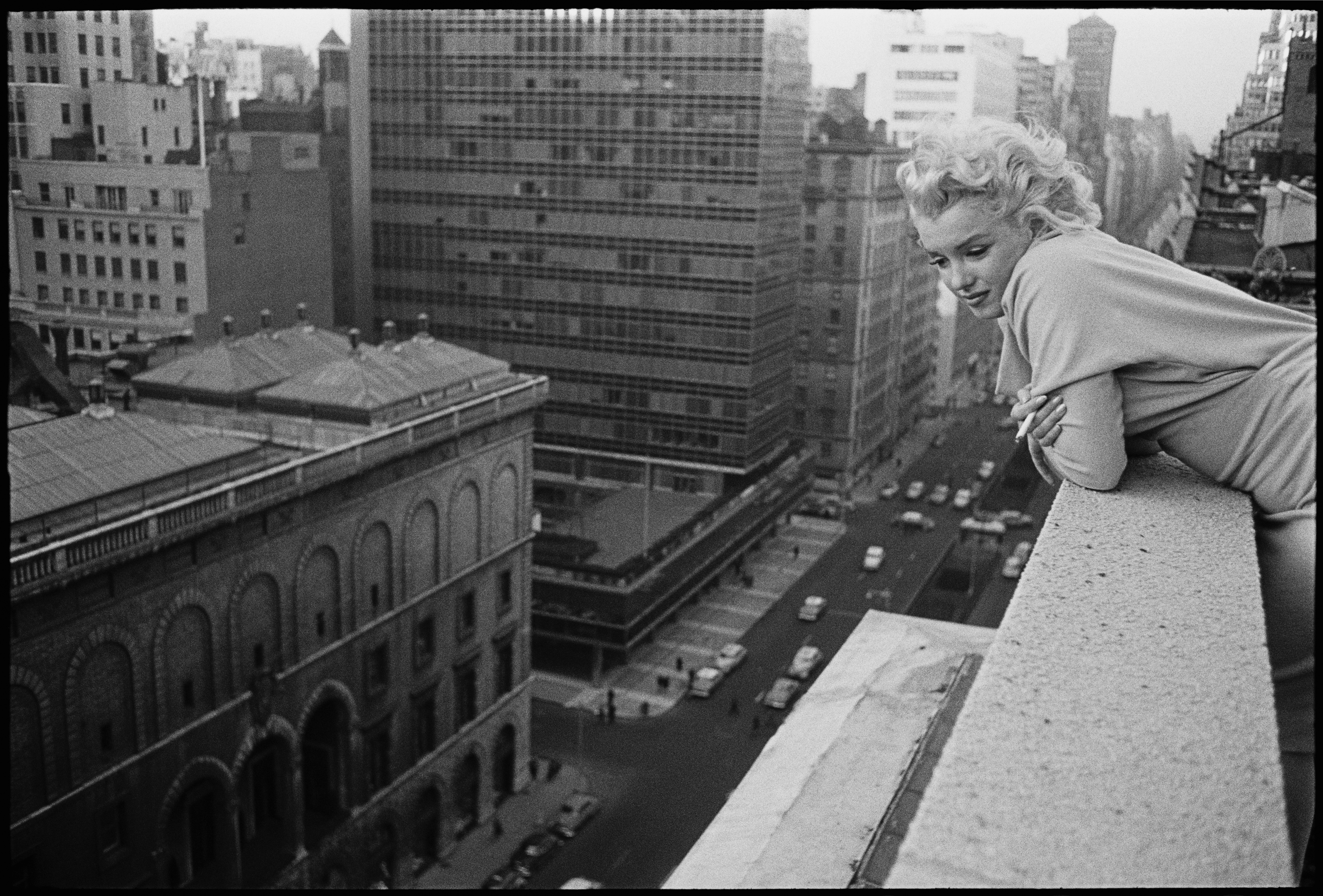 Všední den. Momentka s Marilyn Monroe, jak se vyklání z balkonu hotelu Ambassador. Březen 1955 v New Yorku.